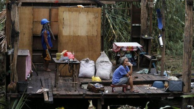 Woman sits in ruined house in Taft, Samar, Philippines (7 Dec 2014)