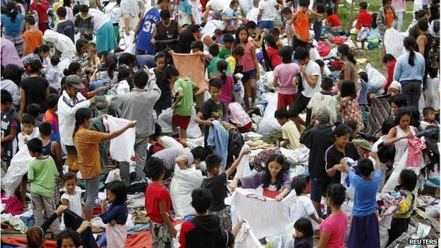 People sort through donated clothes at an evacuation centre near Manila (8 Dec 2014)