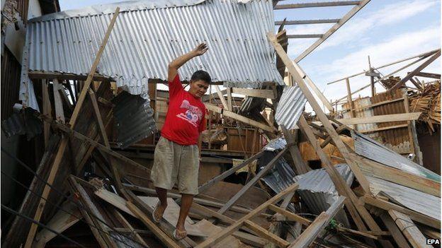 Man climbs over fallen building in Dolores, Samar island (8 Dec 2014)