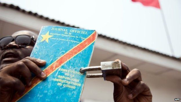 A protester holds the constitution of the Democratic Republic of Congo locked with a padlock in front of the UNC opposition party's headquarters in Barumbu, near Kinshasa, on 13 September 2014