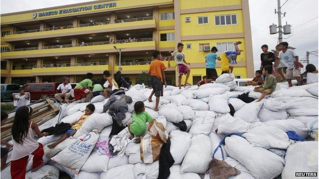 Children play atop sacks of donated clothes at an evacuation centre for the coastal community to take shelter from Typhoon Hagupit, in Manila 8 December 2014