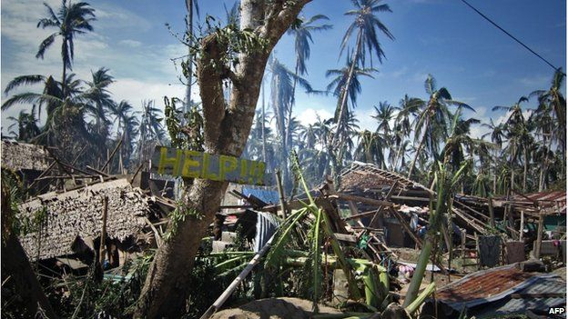 Destroyed houses and trees with a slogan calling for help are seen along a road in the village of Mantang, Taft town Eastern samar province central Philippines on 8 December 2014, a day after typhoon Hagupit hit the province