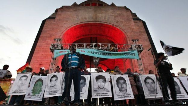 Felipe de la Cruz, the father of one of the 43 missing students, speaks to a crowd in front of other relatives holding posters of their missing loved ones, during a protest at the Revolution Monument in Mexico City on 6 December, 2014