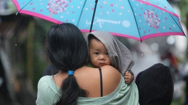 A young boy is carried by his mother as they return to their homes in Legazpi, Albay province, eastern Philippines on Dec 8