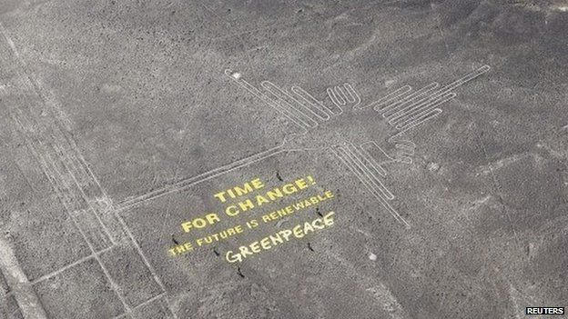 """Greenpeace activists stand next to massive letters delivering the message """"Time for Change: The Future is Renewable,"""" next to the hummingbird geoglyph in Nazca on 8 December, 2014"""