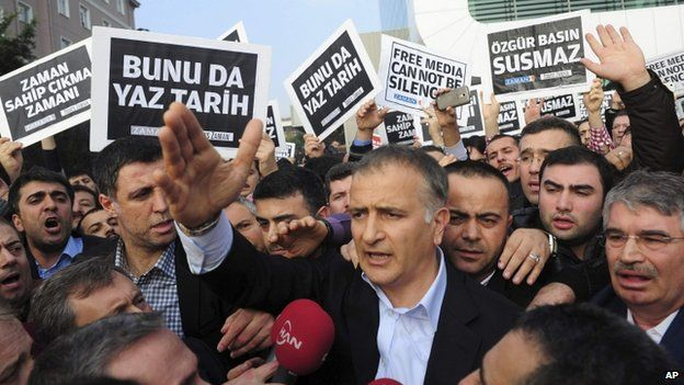 Zaman editor-in-chief Ekrem Dumanli (c) with supporters after leaving Zaman newspaper HQ in Istanbul