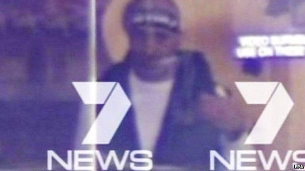 A screen grab from Channel 7 News, Sydney, of a man believed to be a gunman inside the Lindt Cafe in Martin Place, Sydney, 15 December 2014