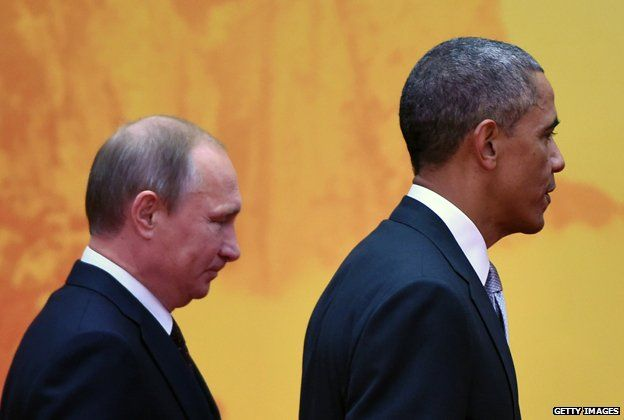 US President Barack Obama walks to a group photo session with Russian President Vladimir Putin (L) at the Asia-Pacific Economic Cooperation (APEC) summit at Yanqi Lake, north of Beijing on November 11, 2014.