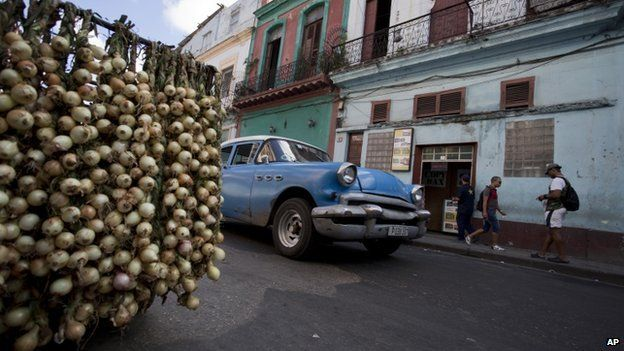 A classic American car passes by a stall selling onions in Havana, Cuba, on 17 December 2014.
