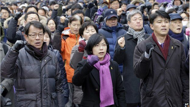 Lee Jung-hee, centre, a head of the Unified Progressive Party, and supporters shout slogans against constitutional court's verdict near the constitutional court in Seoul, South Korea, Friday, 19 December 2014
