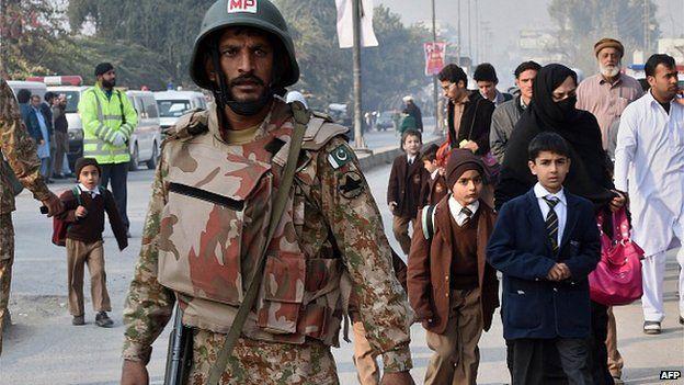 Children walk past a Pakistani soldier after the massacre