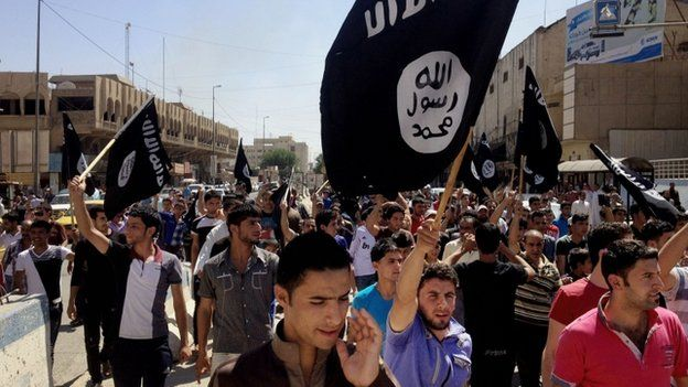 Demonstrators carry Islamic State flags in front of the provincial government headquarters in Mosul