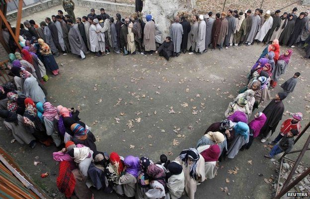 Kashmiri people wait in queues outside a polling station to cast their votes during the fourth phase of the state assembly election in Srinagar December 14, 2014.