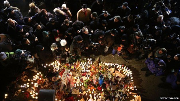 Residents, clergy, police and others converge around a memorial during a vigil to the fallen New York City police officers at the location where they were killed 21 December 2014