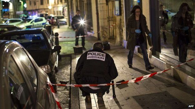 Policemen collect evidence on the site where a driver ploughed into a crowd injuring 11 people, Dijon, 21 December 2014