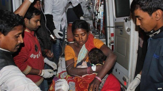 An injured women and her child arrive at a hospital in the Sonitpur district of Assam on December 23, 2014
