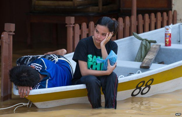 A woman (C) looks on as she waits inside a boat as her house submerged in floodwaters in Pengkalan Chepa, near Kota Bharu on December 27, 2014