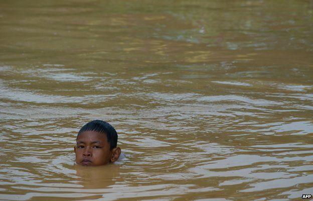 A boy plays in floodwaters in Pengkalan Chepa, near Kota Bharu on December 27, 2014