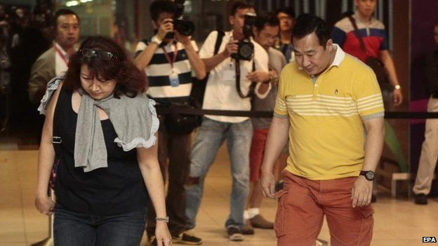A couple head to a cordoned off area at Changi airport in Singapore, 28 Dec