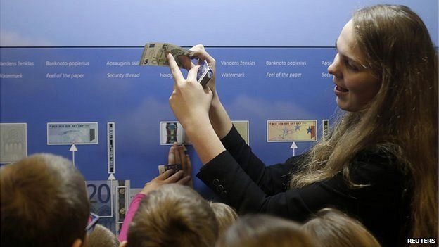 A guide shows the security features of euro banknotes to students in Vilnius 17 Dec 14