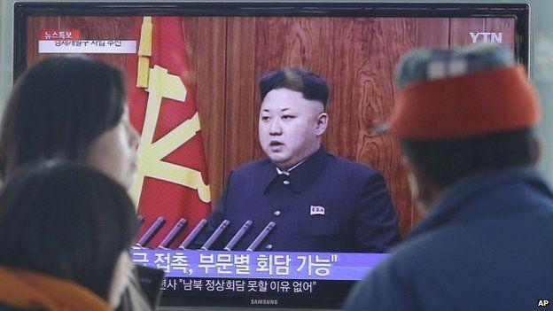 Passers-by at a Seoul train station watch Kim Jong-un's speech