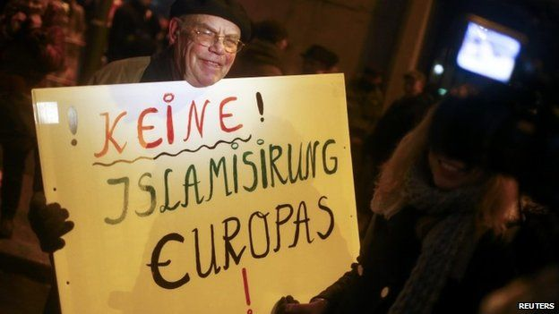 """A man holds a sign reading """"No to Islamisation of Europe!"""""""