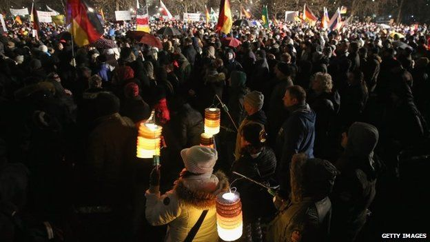 Supporters of the Pegida movement, including some holding lanterns glowing in the colours of the German flag, gather for another of their weekly protests on January 5, 2015 in Germany