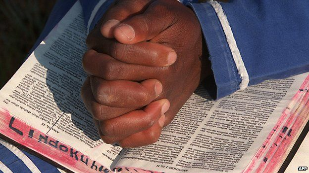 A South African praying with a Bible - archive shot