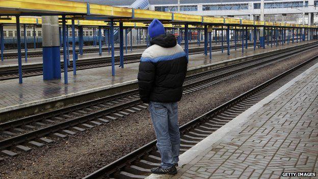 A man stands on a platform at an empty main railway station in Simferopol, Crimea