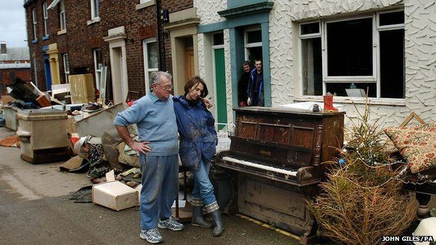 Residents of Carlisle look on as a stockpile of furniture and possessions ruined by the water awaits collection