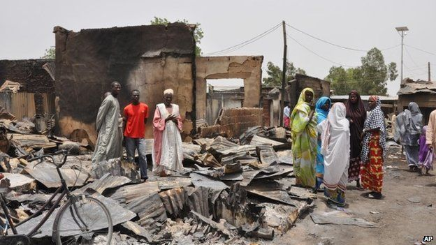 People stand outside burnt houses following an attack by Islamic militants in Gambaru, Nigeria (11 May 2014)