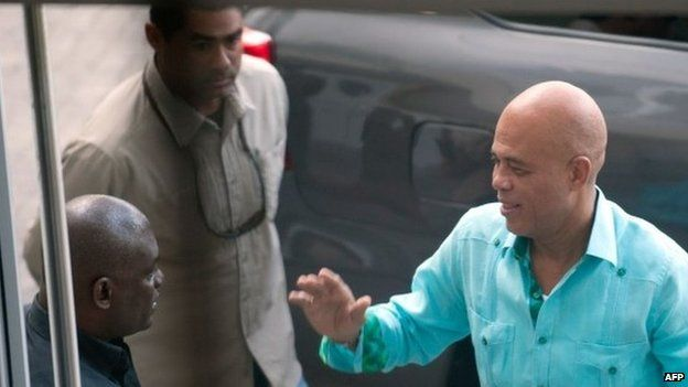 Haitian President Michel Martelly (right) arrives for meetings with members of opposition parties in Port-au-Prince on 17 December 17 2014