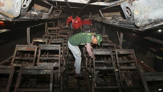 Pakistani rescue workers search through the wreckage of a passenger bus destroyed after colliding with an oil tanker on a highway near Karachi, Pakistan - 11 January 2015
