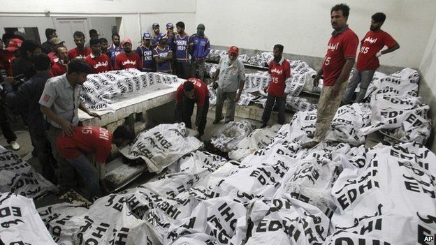 Pakistani rescue workers gather around the bodies of bus accident victims in a hospital in Karachi, Pakistan - 11 January 2015