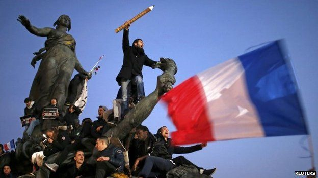 A man holds a giant pencil as he takes part in a solidarity march (Marche Republicaine) in the streets of Paris, 11 January 2015