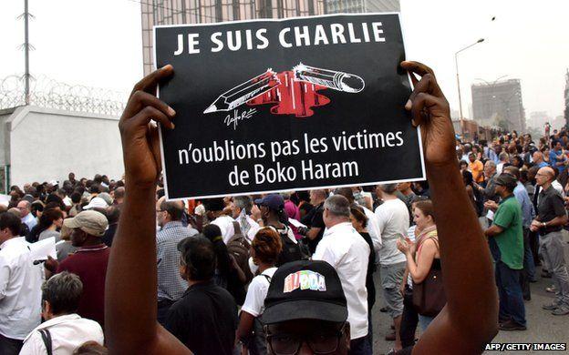 "Man holding a sign that says: ""Je suis Charlie n'oublions pas les victimes de Boko Haram"""