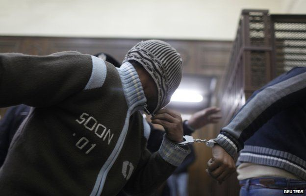 Defendants enter a cell a few minutes before they hear the verdict at a court in Cairo January 12, 2015