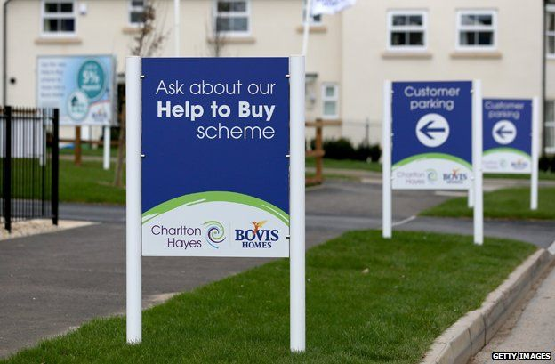 """Signs outside newly built homes read """"Ask about our Help To Buy scheme"""""""