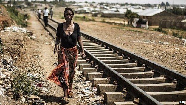 A woman walks next to train tracks in Zambia on 12 November 2014
