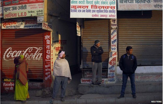 Nepalese stand in front of a closed shops as they look towards protesters (unseen) during the general strike in Kathmandu 13 January 2015.
