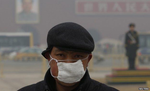 A man wears a mask as he makes his way during a polluted day at Tiananmen Square in Beijing