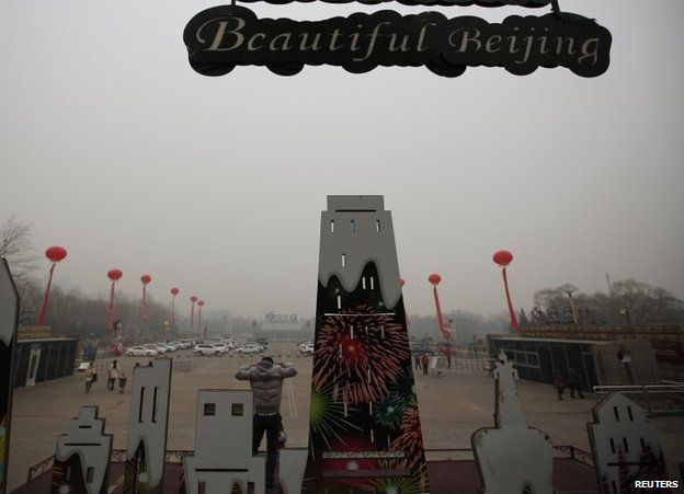 A man stands on a platform as he poses for a picture at an observatory tower during a polluted day in Beijing