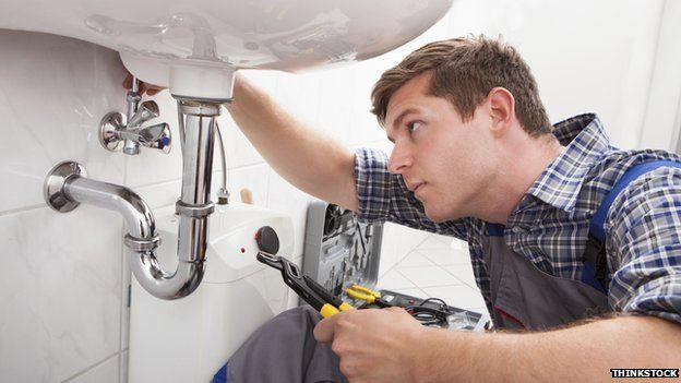 plumber mends sink