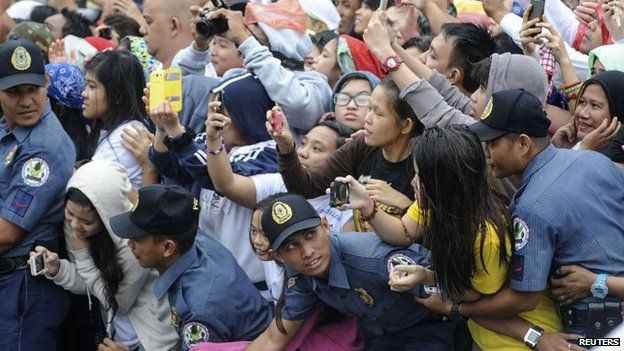 Members of the Philippine National Police prevent well-wishers from moving forward as Pope Francis' motorcade passes by in Manila, 18 January 2015