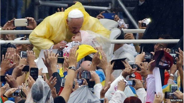 Pope Francis kisses a child as he arrives to lead an open-air Mass at Rizal Park
