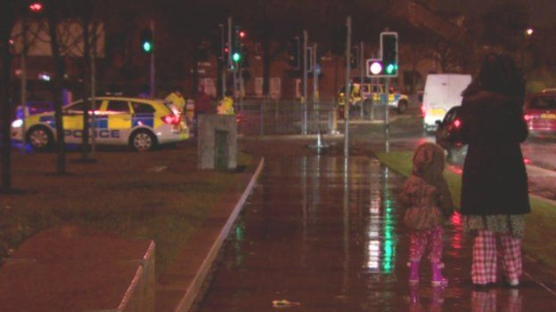 Woman in pyjamas with child at security alert scene