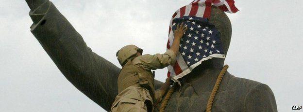 US flag on statue of Saddam Hussein