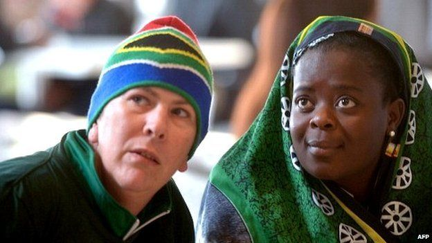 A white man and and a black woman watch the memorial service for Nelson Mandela on television in a bar in Soweto on 10 December 2013 in South Africa