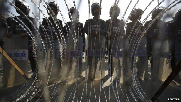 Nepalese riot police personnel stand guard in front of a barricade during a general strike in Kathmandu January 20, 2015.