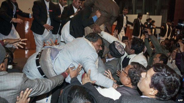 Nepalese constituent assembly members scuffle with security officers at parliament in Kathmandu early on January 20, 2015.